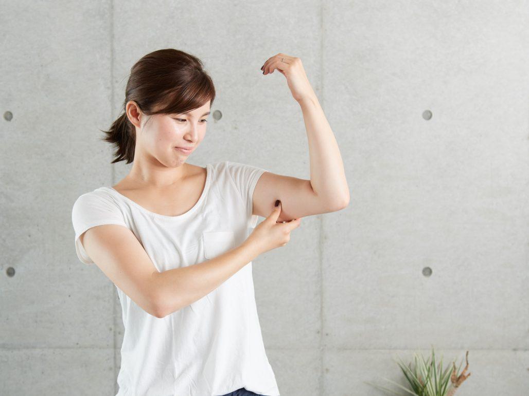 自分の二の腕を触る女性